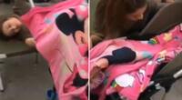La joven estaba dormida mientras mecía el cochecito de su hija.