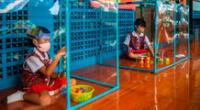 Dos alumnos tailandeses juegan detrás de pantallas de plástico en áreas de juego separadas en la escuela Wat Khlong Toey el 10 de agosto de 2020 en Bangkok, Tailandia.