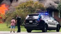 El momento preciso en que la mujer y el policía estadounidense oran en la escena del incendio.