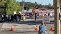 Manifestantes sostienen pancartas cerca de la entrada del centro de vacunación en el estadio de los Dodgers en Los Ángeles, EE.UU., 30 de enero de 2021.