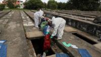 Los sepultureros con trajes protectores manipulan bolsas con huesos durante las exhumaciones en espacios abiertos sobre tumbas de cemento mientras se suspenden nuevos entierros.