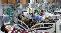 Los trabajadores de la salud atienden a los pacientes infectados con coronavirus COVID-19 en la sala de emergencias.