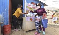 Madre de la olla común entrega ración de alimento a pobladora de San Antonio.