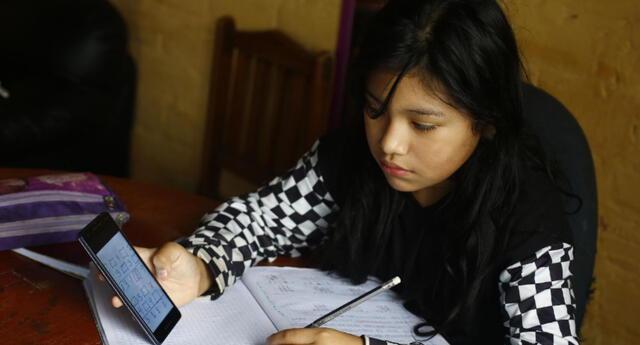 Padres de familia acompañan a sus hijos en clases virtuales o tele educación dentro de su casa.