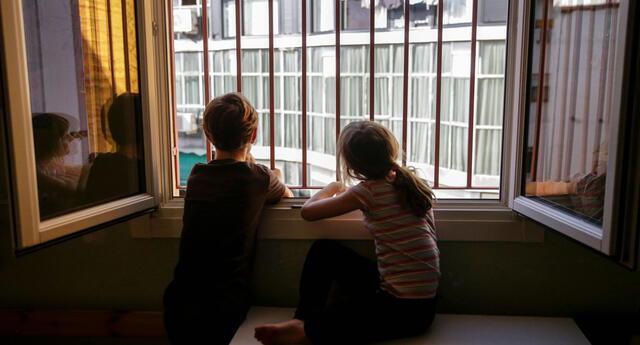 Niños miran por la ventana de su dormitorio durante el confinamiento | Foto: El País/difusión