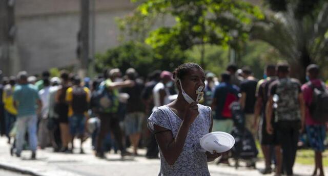 Personas sin hogar reciben almuerzo en el centro de Sao Paulo, Brasil, el 23 de marzo de 2021, en medio de la pandemia de coronavirus.