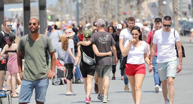 Las personas caminan sin mascarillas cerca de la playa en Tel Aviv. Israel puso fin al uso obligatorio de mascarillas al aire libre tras una exitosa campaña de vacunación contra el coronavirus.