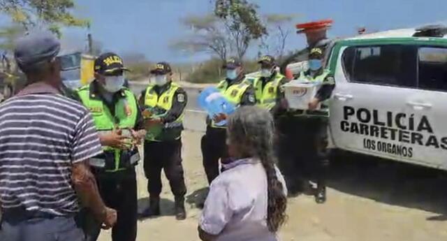 Personas de la tercera edad reciben ayuda de policías en Piura.